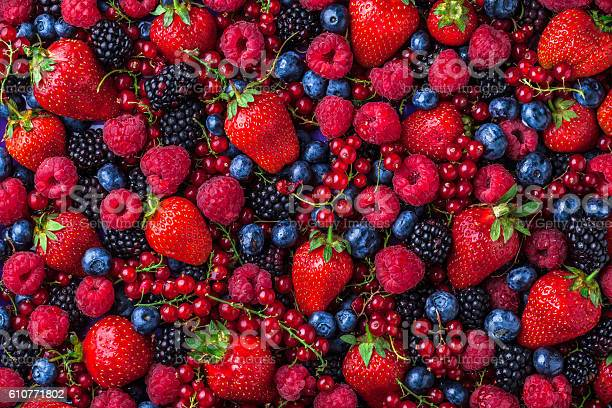 Forest fruit berries overhead assorted mix in studio on dark background with raspberries, blackberries, blueberries, red currant.