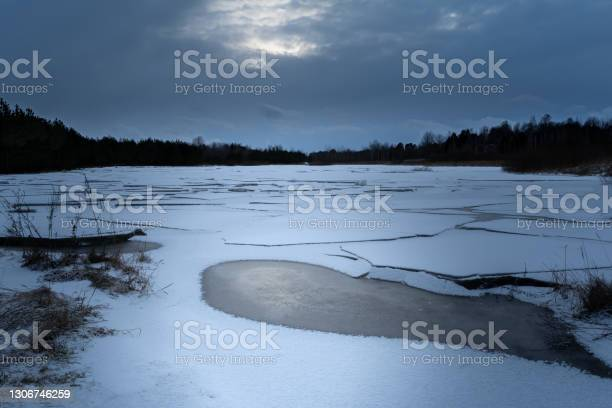Photo of Forest lake with melting blocks of ice, night scene with gloomy sky and moonlight in spring time, nature background
