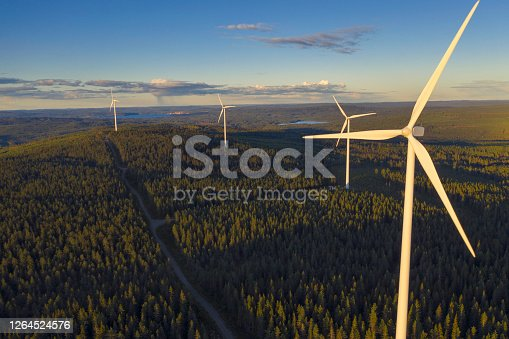 Wind power stations in a forest landscape in the evening in the Dalarna region of Sweden.