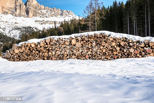 istock Forestry industry: stack of logs in a snowing mountain meadow at the foot of towering peaks 1199737908