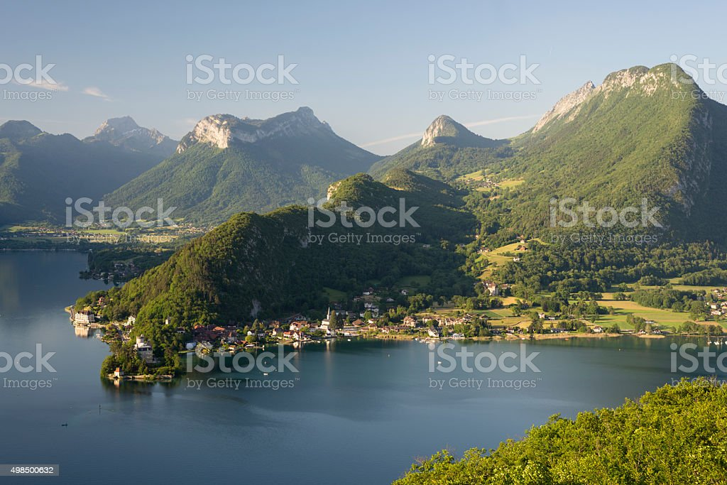 Forests and mountains at the Lake Annecy after sunrise stock photo
