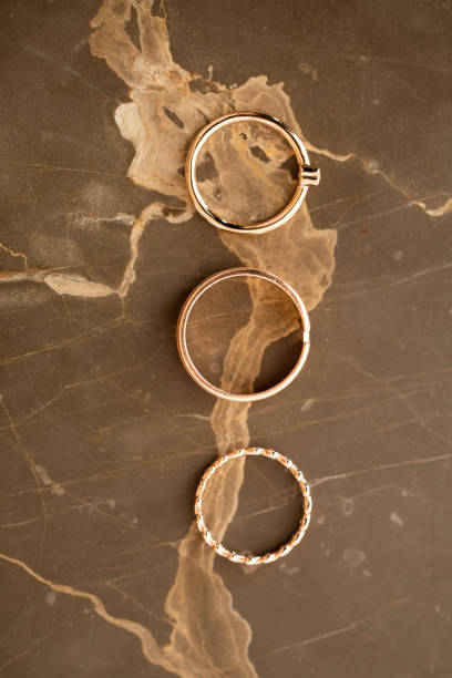 für immer zusammen herz trauringe auf gold marmortisch, symbolisieren liebe und für immer zusammenbleiben, makro - verlobungsring 3 steine stock-fotos und bilder