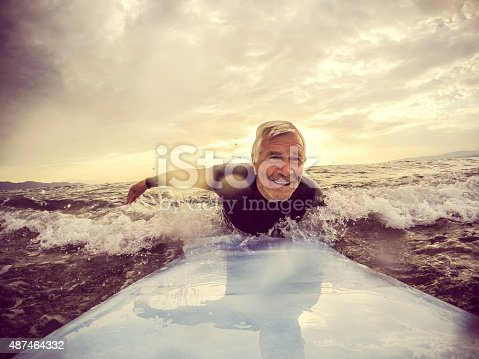 Very active senior man, surfing on a wave with a surfboard