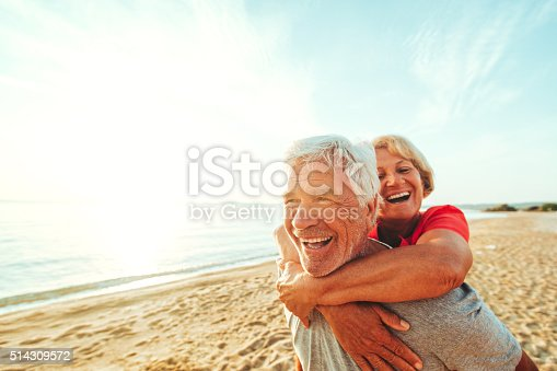 A senior couple seen having fun at the beach on a nice day. The woman is on her husband's back, with her arms crossing over the front of his chest. The sun is glistening on the ocean water.