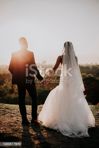 The bride and groom on their most important day in your life. They love each other, holding hands, kissing. It is the wedding dress and he in formal suits. They are ready to say to each other YES.
