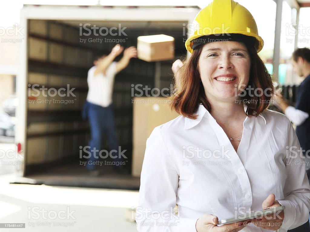 Forewoman with Tablet and Workers Loading Moving Truck royalty-free stock photo