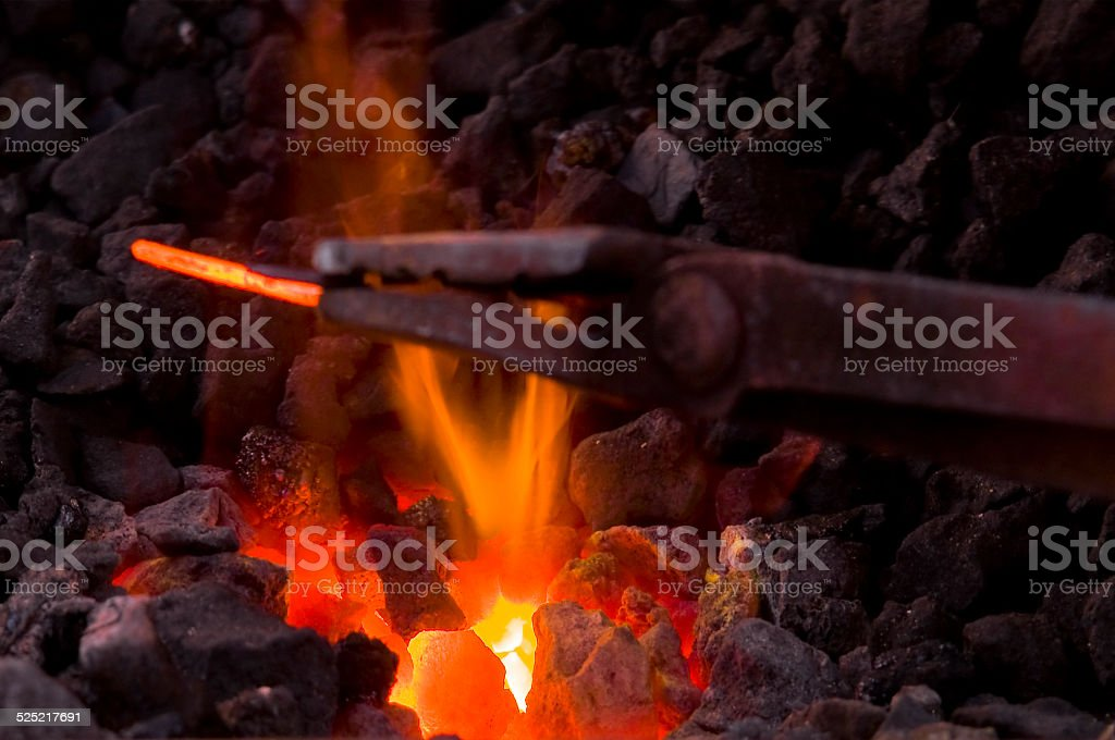 Forge fire with pliers and wrought iron stock photo