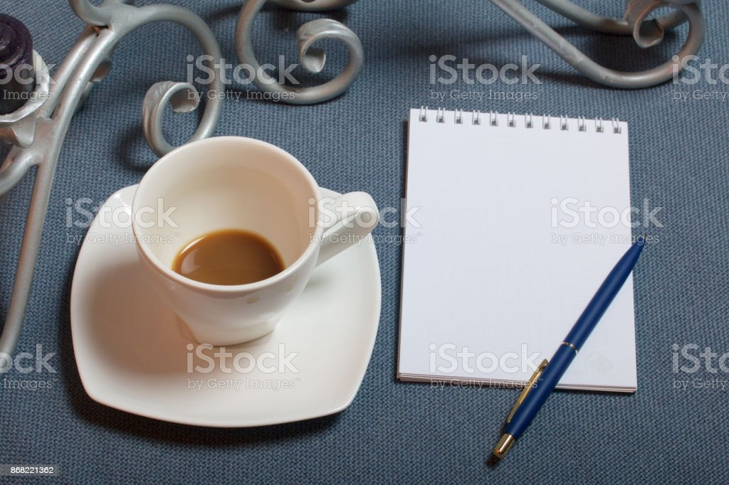 Forged metal candlestick with candles. A cup with unapproved coffee. There is an open notepad and a pen. Fallen autumn leaves of yellow and red are scattered on the surface. stock photo