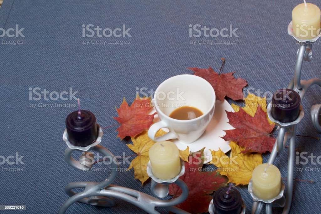 Forged metal candlestick with candles. A cup with unapproved coffee. Fallen autumn leaves of yellow and red are scattered on the surface. stock photo