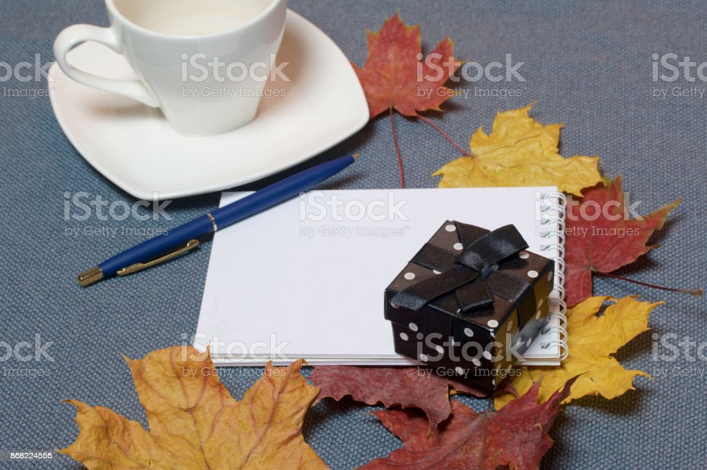 Forged metal candlestick with candles. There is an open notepad and a pen. A cup with unapproved coffee. Fallen autumn leaves of yellow and red are scattered on the surface. stock photo