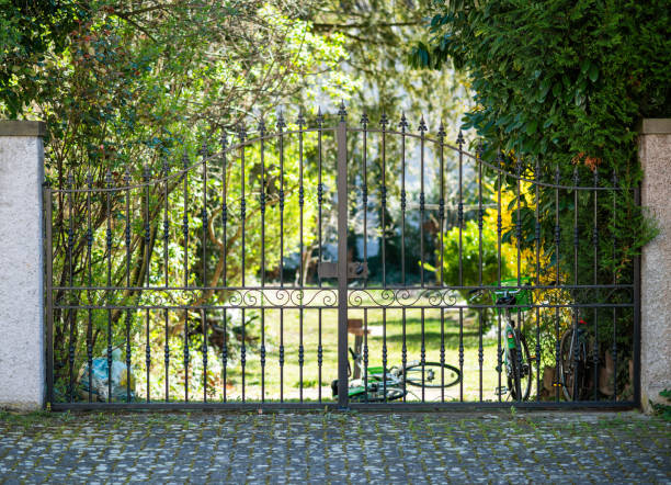 forged steel gate entrance to luxury garden with multiple bicycles parked behind