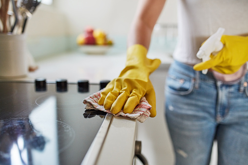 Cropped shot of a woman cleaning a kitchen counter at home