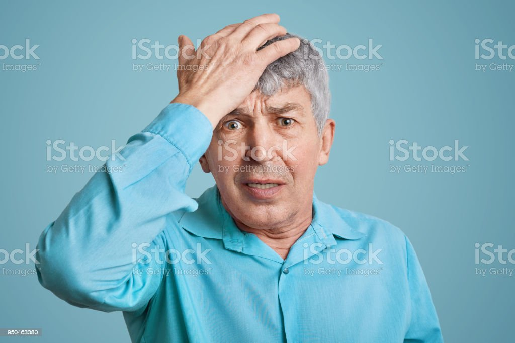 Forgetful handsome elederly wrinkled man in blue shirt, keeps hand on head, feels desperately as forgets about important meeting, isolated over blue background. Amnesia and old age concept stock photo