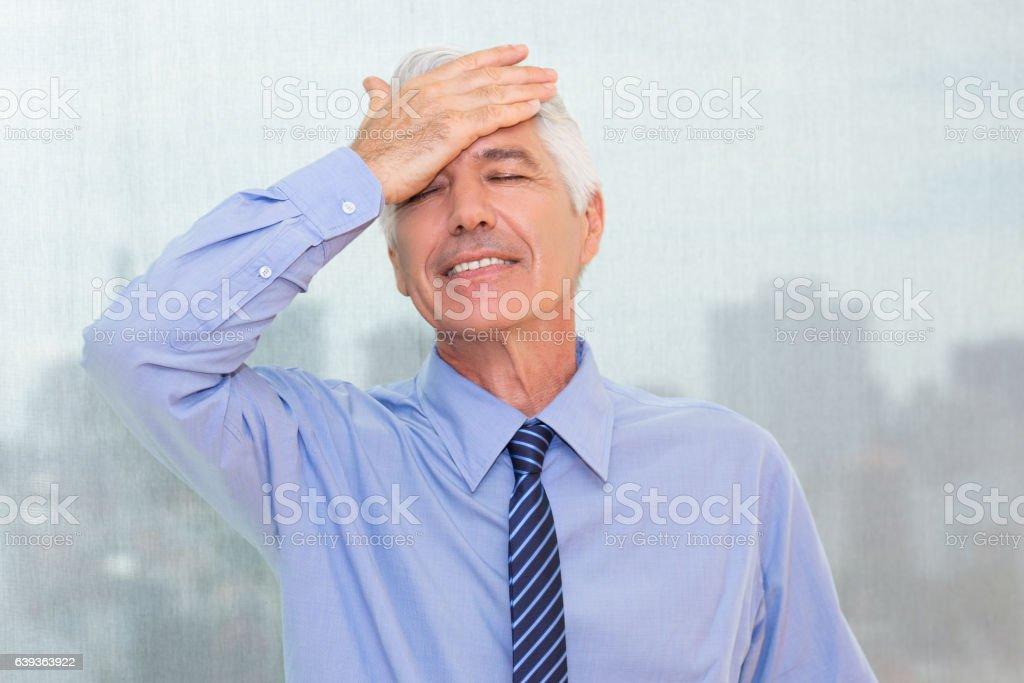 Forgetful senior businessman slapping forehead stock photo
