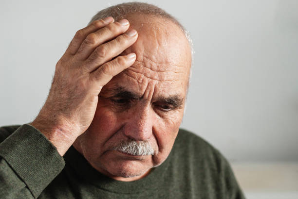 Forgetful senior man holding a hand to his head stock photo