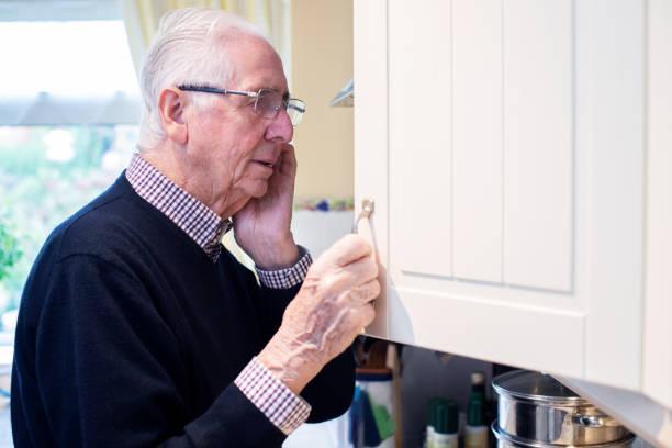 Vergesslich Senior Mann mit Demenz Suchen in Schrank zu Hause – Foto