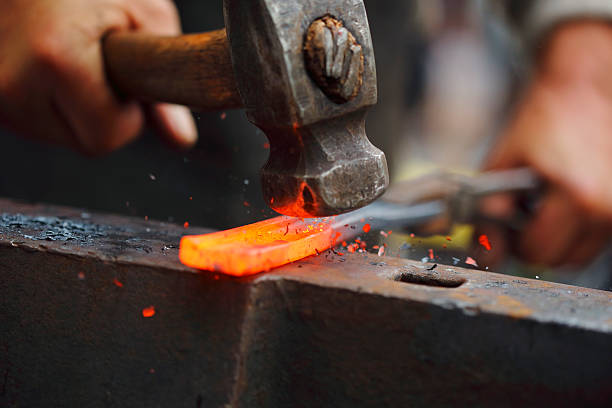Forging hot iron Detail shot of hammer forging hot iron at anvil anvil stock pictures, royalty-free photos & images