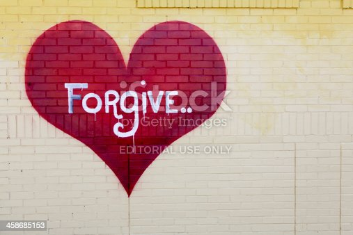 Raleigh, NC, USA - April, 4, 2011. Graffiti on abandoned warehouse gives a simple message: forgive. Local graffiti artists make their mark around the city\'s urban areas.