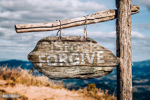 Forgive text on a wooden sign board.