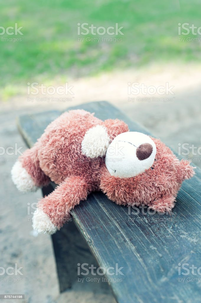 Forgotten childhood. Teddy bear toy lying on the wooden bench. stock photo