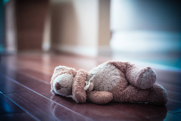 Forgotten Teddy Bear Forlorn old worn teddy bear left in empty room teddy bear stock pictures, royalty-free photos & images