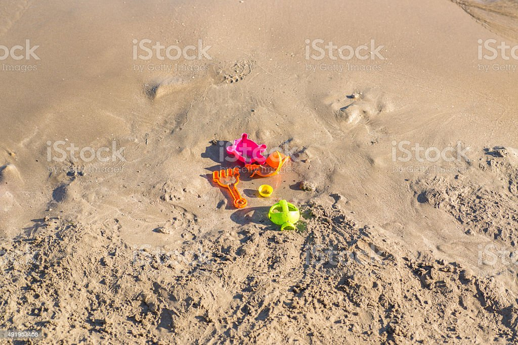 forgotten toys on a sandy beach stock photo