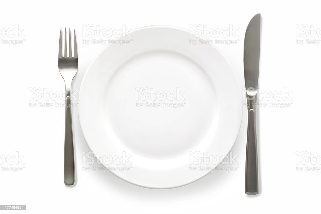 A fork and a knife beside a white plate stock photo