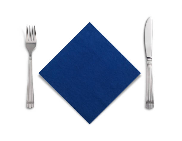 Fork and knife in a blue cloth isolated on white stock photo