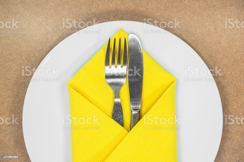 fork and knife in yellow napkin on white plate royalty-free stock photo
