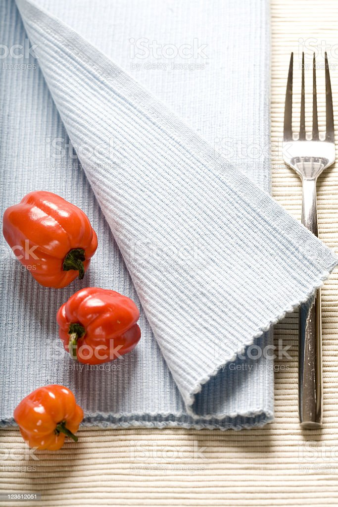 fork and red peppers on blue napkin royalty-free stock photo