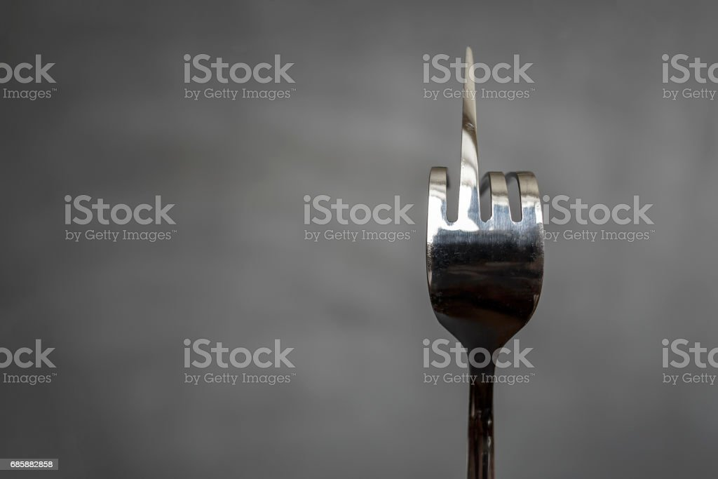 Fork bent in the form of an obscene gesture sign of the middle finger on a blurred background stock photo