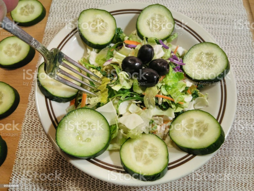 Fork Getting Ready To Dig Into A Healthy Chef Salad Garnished With Cucumbers stock photo