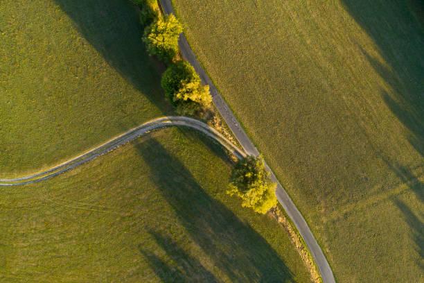 Gabel in eine Straße durch Felder und Wald - Luftbild – Foto