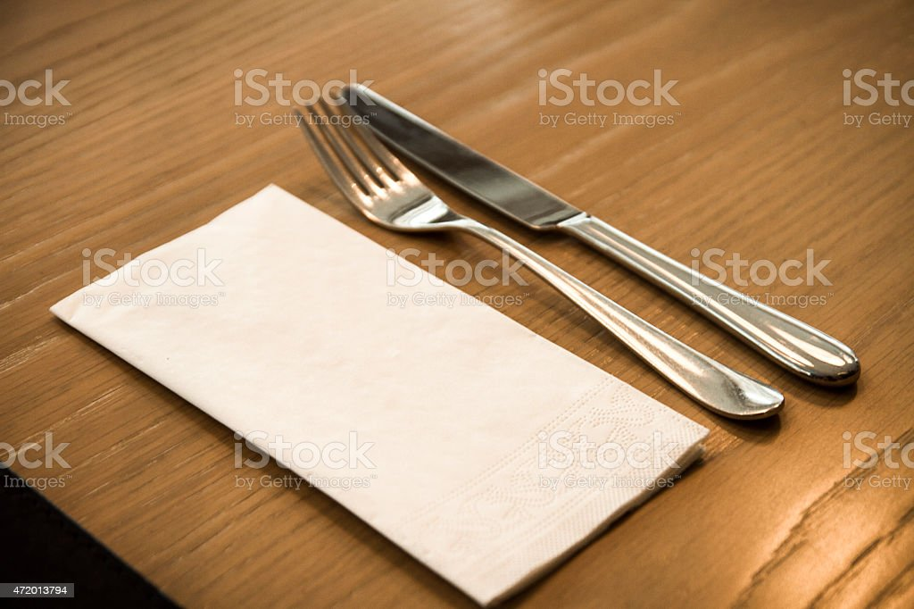 Fork, knife and paper napkin on a wooden table. stock photo