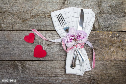 Fork, knife, orchid on white checkered napkin with a red ribbon and red hearts. Table setting for a wedding or Valentine's Day