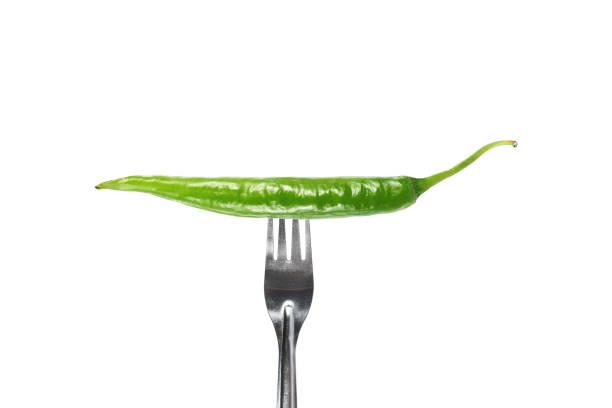 gabel sticht grünen chili, isoliert auf weiss - peperoni stiche stock-fotos und bilder