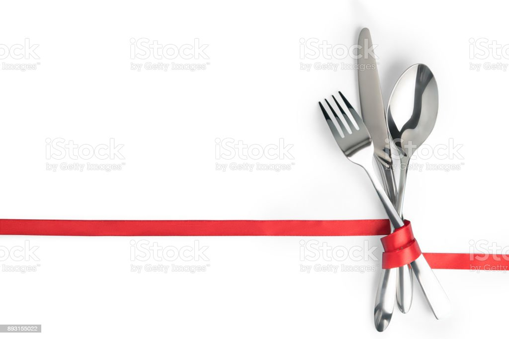 Fork, spoon and knife tied with a red ribbon isolated with copy space stock photo