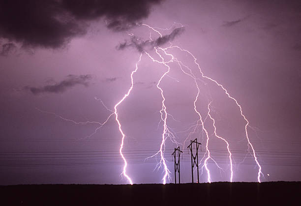 Forked lightning behind power lines stock photo