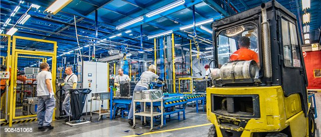 istock Forklift and manual workers in a factory 908451068