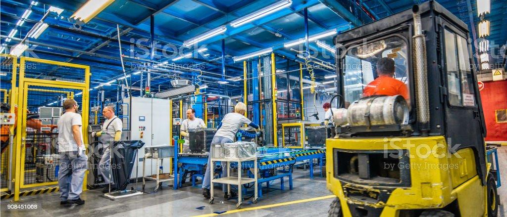 Gabelstapler und manuelle Arbeiter in einer Fabrik – Foto