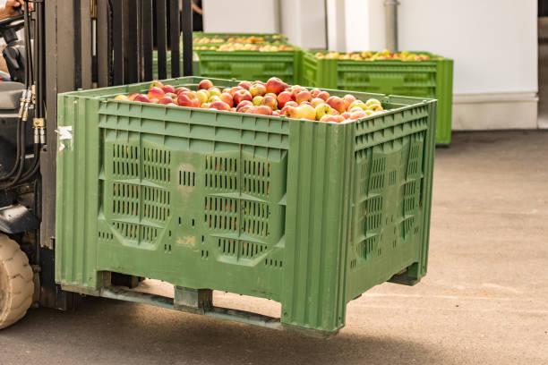Gabelstapler trägt Obstkisten. Viele Äpfel im Container – Foto