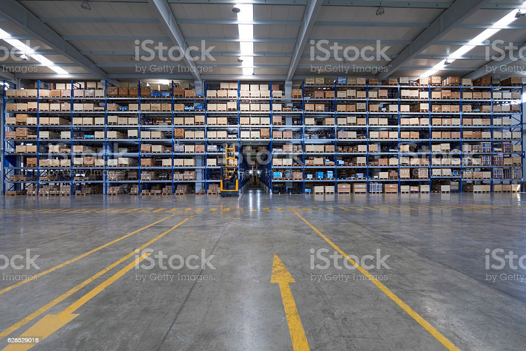 Forklift carrying cardboard box in warehouse. stock photo
