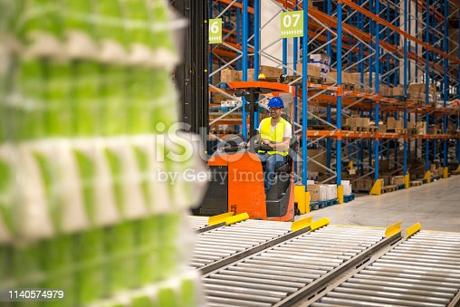 Warehouse worker in protective workwear driving forklift and manipulating goods in storage facility.