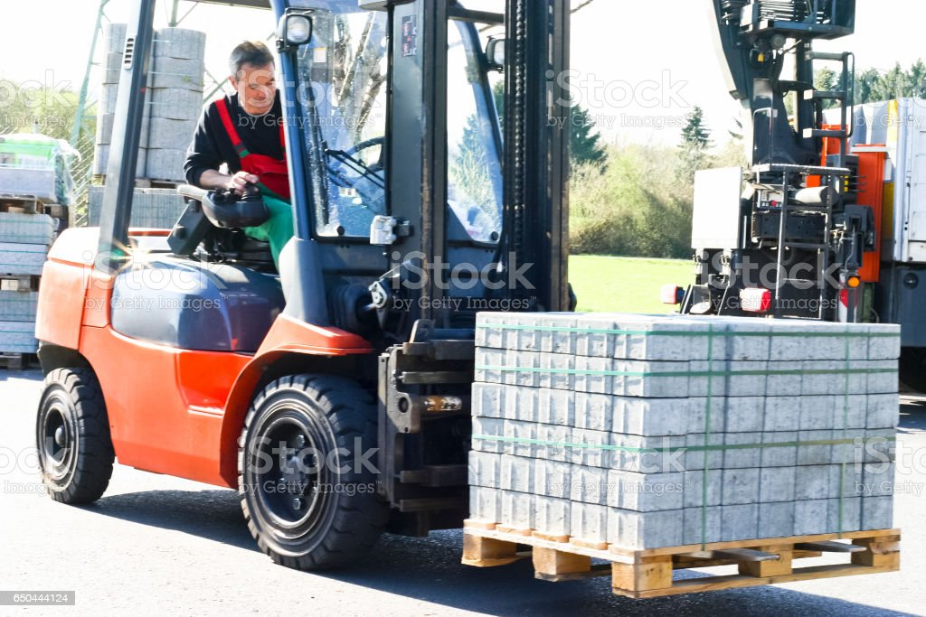 Forklift Driver Loading a Pallet of Paving Stones stock photo