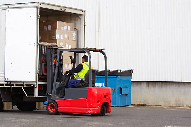 a forklift driver loading a truck - lorries unloading stock photos and pictures