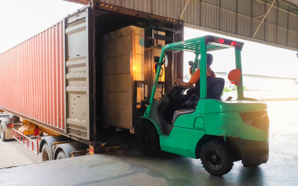 forklift driver loading goods pallet into the truck container, freight industry warehouse logistics and transport - caricare attività foto e immagini stock