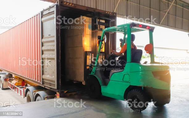 Photo of Forklift driver loading goods pallet into the truck container, freight industry warehouse logistics and transport