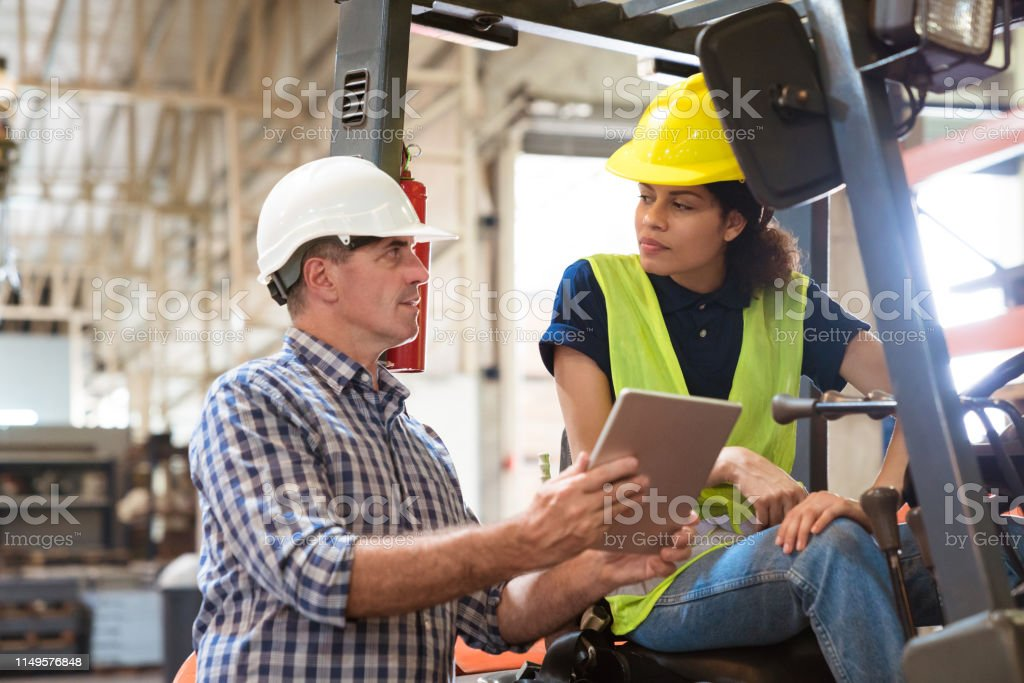 Forklift driver looking at manager in industry Manager and female engineer discussing over digital tablet. Forklift driver is looking at foreman. They are in manufacturing industry. 30-34 Years Stock Photo