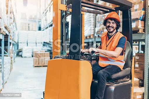 Smiling young man driving a forklift in a warehouse