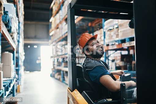 Close up of a young male forklift driver working in a warehouse